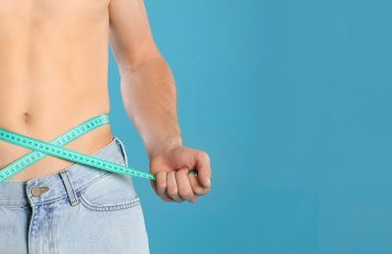 Man measuring waist size